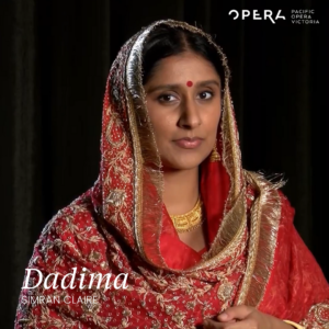 Simran looks directly into the camera wearing a red and gold sari with intricate gold beading and detailing.