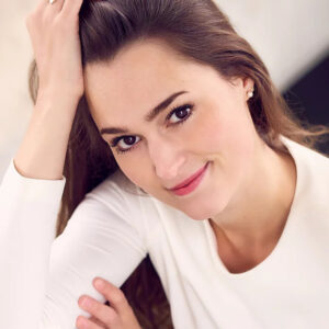 Claire wears a white long sleeve shirt and is resting her head on her hand as she looks directly into the camera, giving a relaxed and welcoming feeling that is amplified by the bright even lighting. She has long straight brown hair and a slight smile on her face.