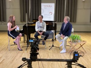 Three people sit with glass COVID safety dividers between them, a piano and the Opera Etc. banner behind them. A camera is in the forefront of the image, filming thte three subjects as they talk about all things opera.