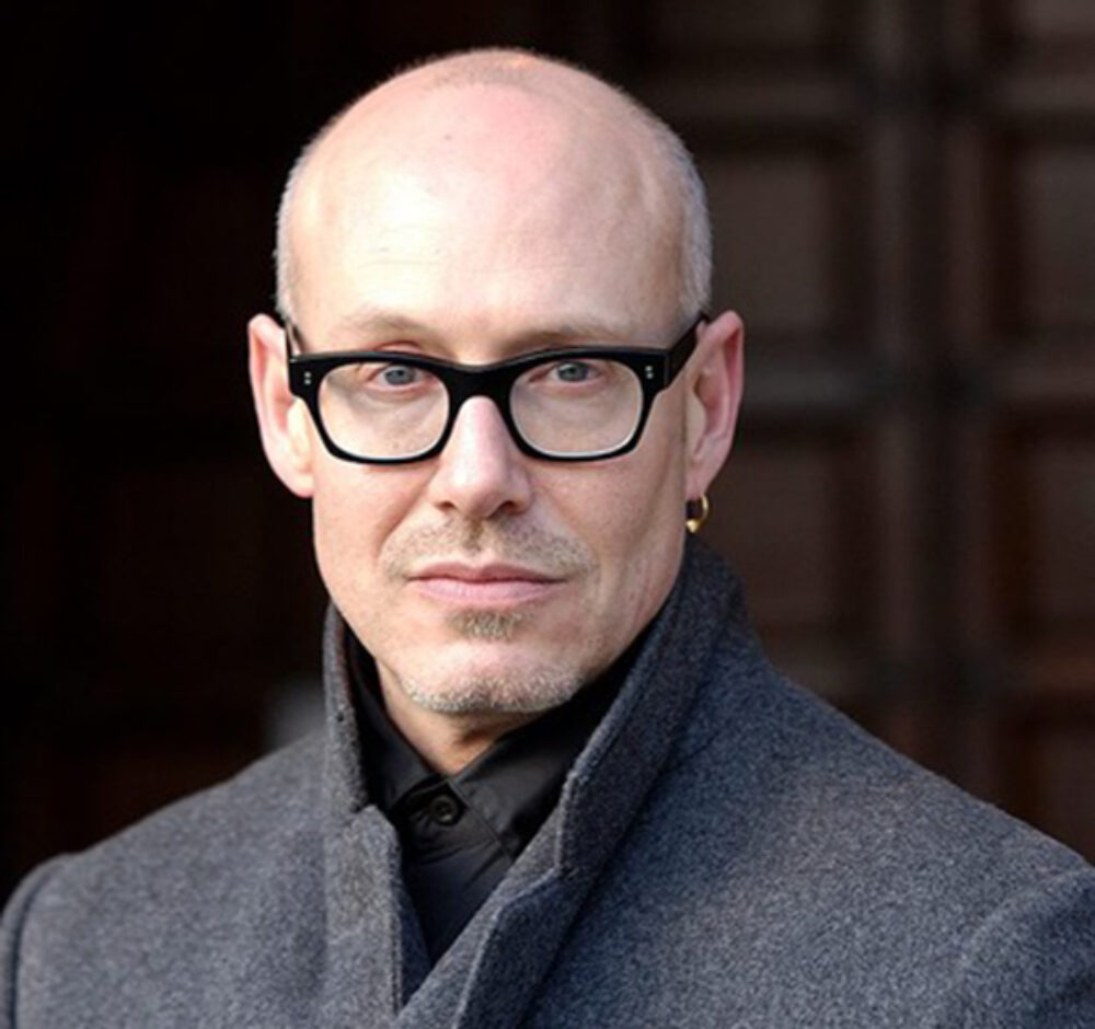 Tom Diamond looks into the camera with a serious expression on his face and a dark, moody background behind him. He wears thick glasses and is dressed immaculately in a gray jacket and black button up shirt.