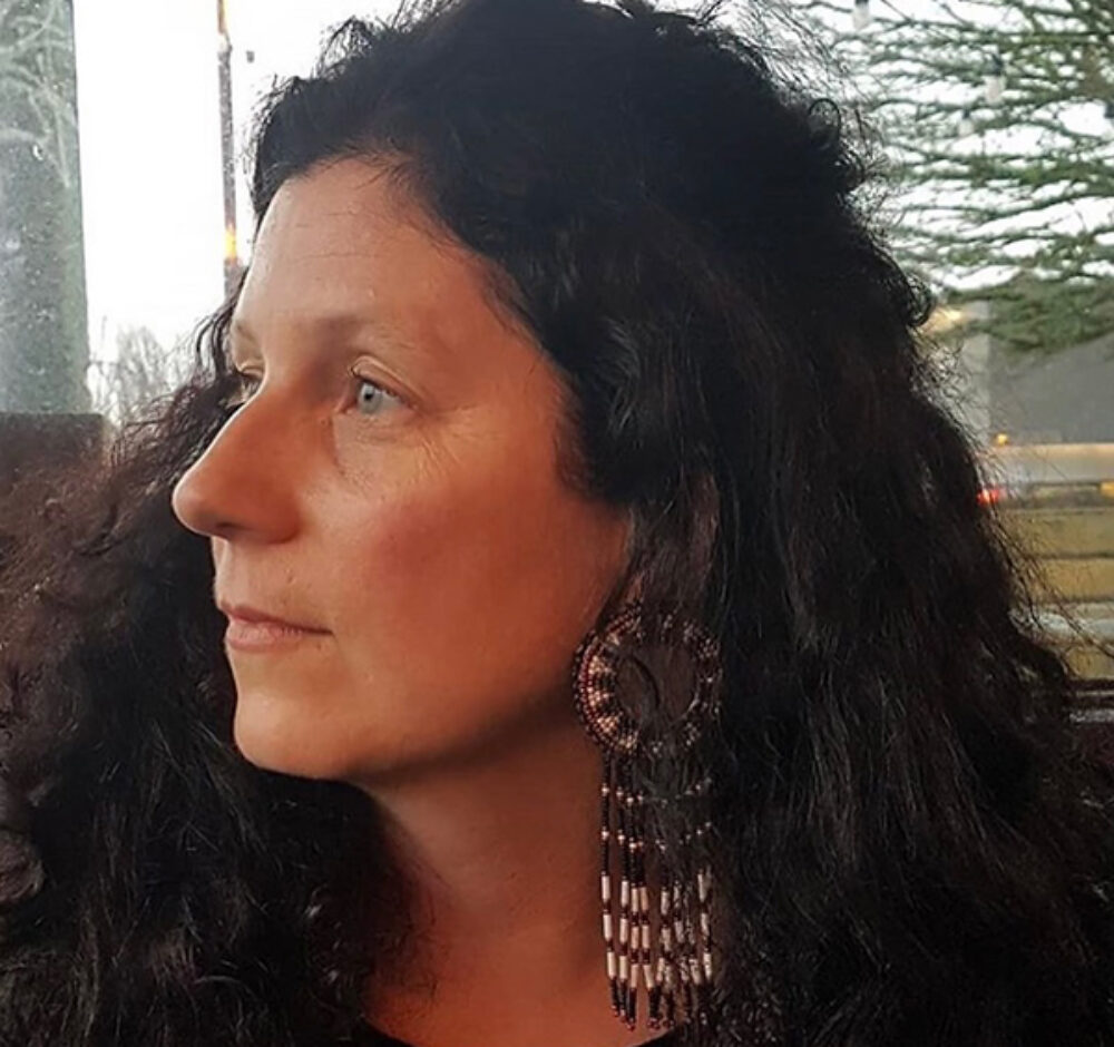 A close up shot of Sarah, she looks off into the distance to the left. She has her hair swept behind her ear to showcase beautifully intricate beaded earrings.